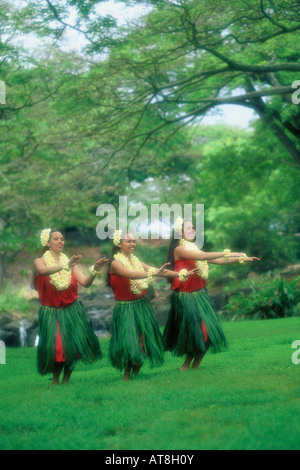 Three Hula Dancers in ti leaf skirts and yellow plumeria leis performing an Auana style hula - Stock Photo