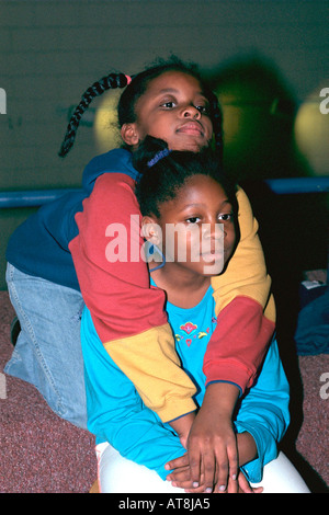 Black girl giving sister a warm embrace ages 7 and 12. Youth Express After School Study Program St Paul Minnesota - Stock Photo