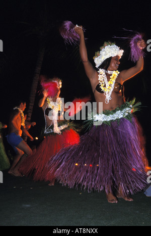 Two colorful female Tahitian dancers shake to the beat while a male dancer wearing shorts and a lei performs in - Stock Photo