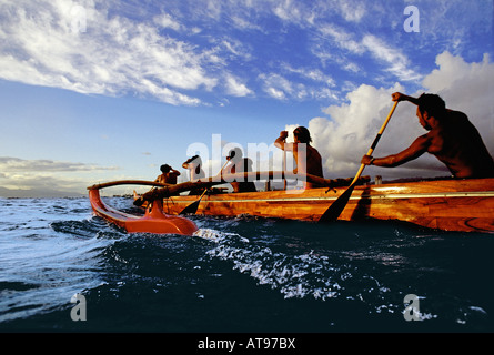 Paddlers in a koa canoe off Waikiki Beach on a beautiful afternoon, photographed from water level. - Stock Photo