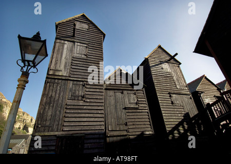 Victorian Net Shop huts in the Old Town by Hastings beach The tall black wooden net shops were built to store fishing - Stock Photo