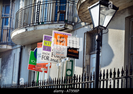 Estate Agents For Sale For Rent and Sold signs outsde Victorian houses in Pelham Crescent on the seafront in Hastings - Stock Photo