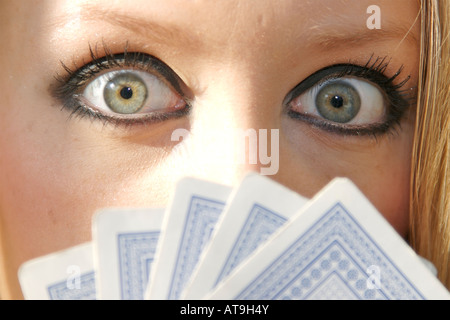 A blonde girl playing cards and staring into the camera - Stock Photo