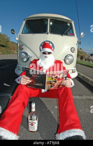 Santa reading magazine in front of old VW camper van. - Stock Photo