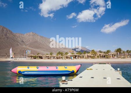 Taba Heights Sinai Peninsula Egypt View along jetty to Red Sea Waterworld centre on quiet beach - Stock Photo