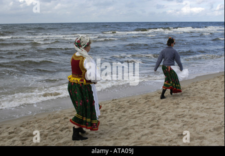 Two women of a local costume group walking at a beach in Miedzyzdroje, Poland - Stock Photo