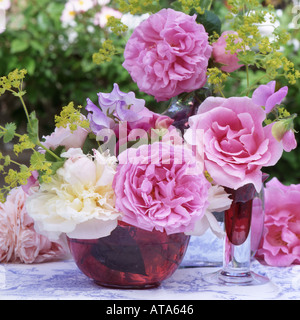 A floral still life with roses paeonies and sweet peas and cranberry glass in an English Garden