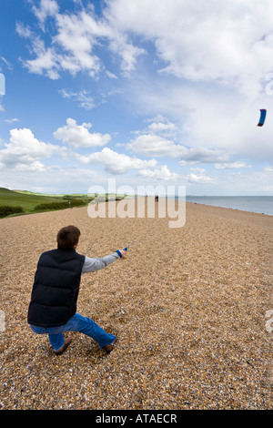 A youth flying a power kite on Chesil Beach, Dorset - Stock Photo