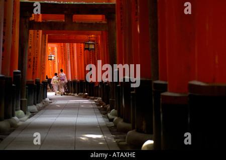 Women in Kimono's walk along a path lined with Torii gates Fushimi Inari Shrine Kyoto Japan - Stock Photo