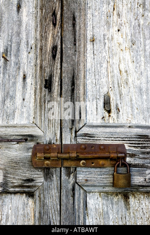 Old wooden door with a rusty padlock - Stock Photo