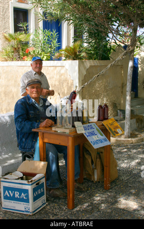 A Greek man selling wine in the street at Pyrgos in Santorini. - Stock Photo