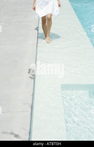 Woman walking on shallow swimming pool ledge, cropped view - Stock Photo