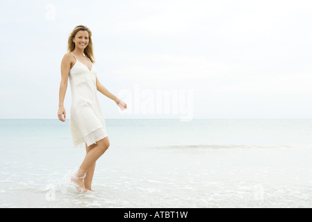 Young woman in sundress walking in shallow water, smiling at camera - Stock Photo
