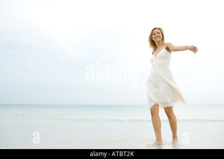 Young woman in sundress walking in surf, arms out, looking away - Stock Photo