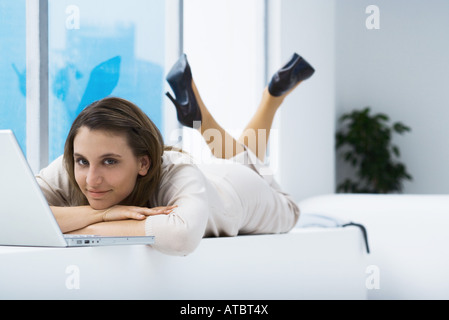 Woman lying on stomach near laptop, smiling at camera - Stock Photo