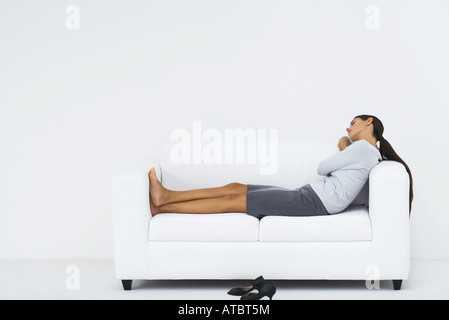 Woman resting on sofa, full length - Stock Photo