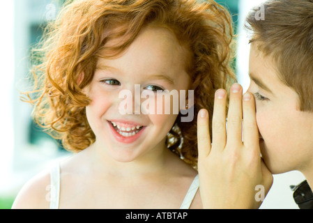 Boy whispering in girl's ear, close-up - Stock Photo
