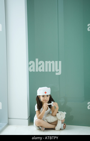 Little girl wearing nurse's hat, sitting on the ground with teddy bear on lap - Stock Photo