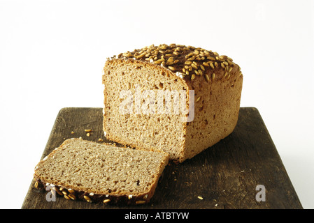 Whole wheat bread loaf and slice on cutting board - Stock Photo