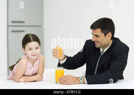 Father and daughter sitting together at table, man squeezing orange juice into glass, girl smiling at camera - Stock Photo