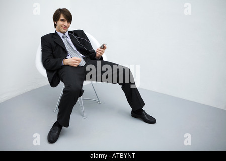 Young man in suit leaning back in chair, listening to mp3 player, smiling at camera, full length - Stock Photo