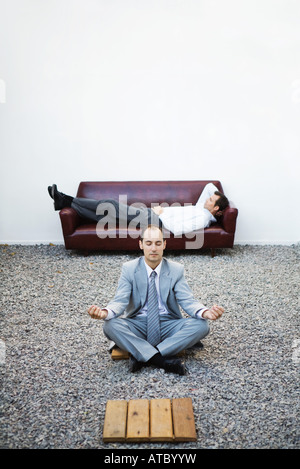 Businessman sitting in lotus position on gravel, eyes closed, colleague lying on couch in background - Stock Photo