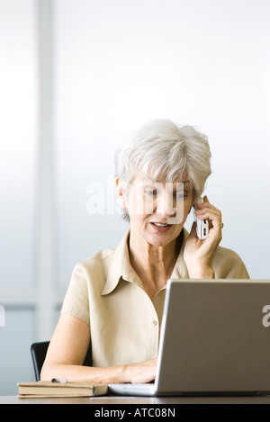 Senior woman using cell phone and laptop computer, looking down - Stock Photo