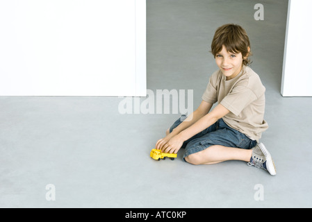 Little boy sitting on the ground, playing with toy truck, smiling at camera - Stock Photo
