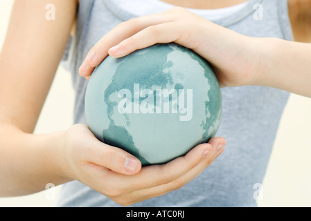 Woman holding globe in cupped hands, close-up, cropped view - Stock Photo