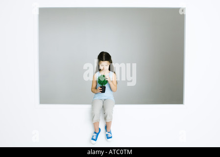 Little girl sitting, holding potted plant, looking down - Stock Photo
