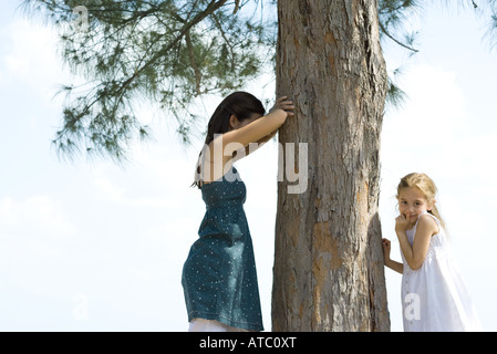 Two young friends playing hide-and-seek, one placing finger on lips and looking at camera - Stock Photo
