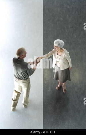 Man shaking woman's hand, high angle view - Stock Photo