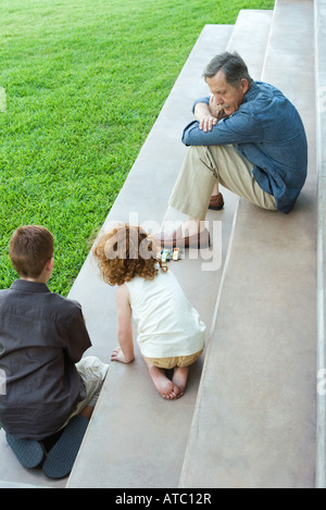 Grandfather and two grandchildren playing with toy cars together on stairs, high angle view - Stock Photo