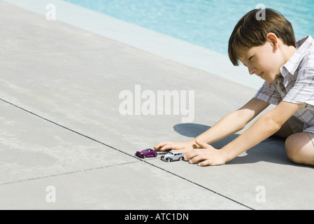 Boy sitting on the ground next to swimming pool, playing with cars, cropped view - Stock Photo