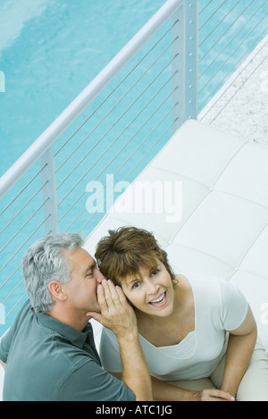 Woman smiling up at camera as her husband whispers in her ear, high angle view - Stock Photo