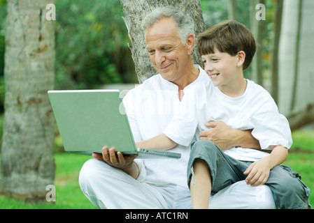 Mature man holding grandson on lap, both looking at laptop computer and smiling - Stock Photo