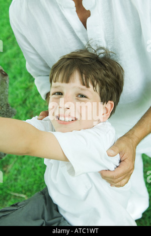 Boy with man's hands on his shoulders, smiling at camera, high angle view - Stock Photo