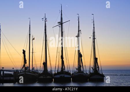 sailing ships at sunrise, harbour of Nes, Netherlands, Ameland - Stock Photo