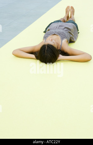 Teenage girl lying on the ground with hands behind head - Stock Photo