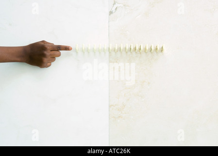 Child reaching toward lined up dominoes, cropped view of hand - Stock Photo