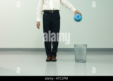 Businessman holding globe over trash can, chest down, front view - Stock Photo