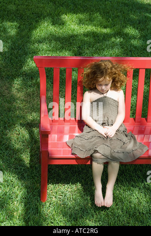 Girl sitting on red bench, high angle view - Stock Photo