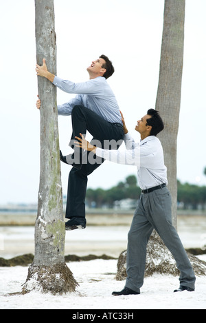 Businessman helping associate climb tree trunk, side view - Stock Photo