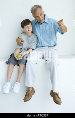 Man sitting with arm around grandson's shoulders, pointing, both looking away - Stock Photo