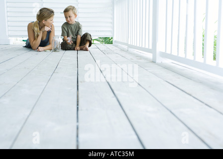 Mother and son on porch together, smiling at each other, boy holding butterfly, low angle view - Stock Photo