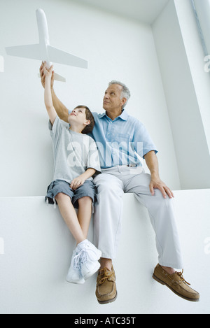 Grandfather and grandson sitting side by side, holding up toy airplane together - Stock Photo