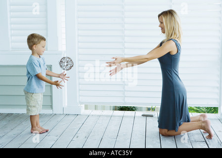 Mother and son face to face, throwing ball, side view - Stock Photo