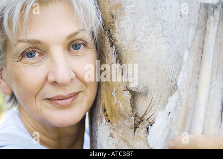 Senior woman leaning against tree trunk, smiling at camera, portrait - Stock Photo