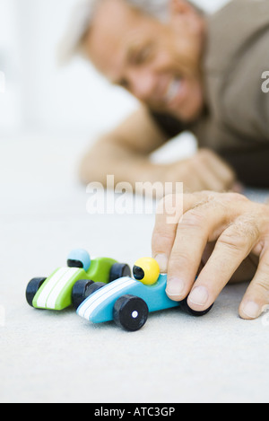 Man playing with toy cars, low angle view, selective focus - Stock Photo