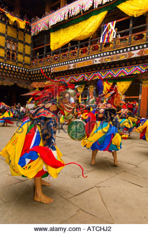 Masked dancers performing the Dance of the Drum from Dramitse during the Paro Tsechu (festival) at the Paro Dzong, - Stock Photo
